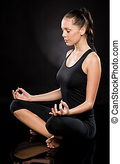 Full length of a young woman meditating with eyes closed