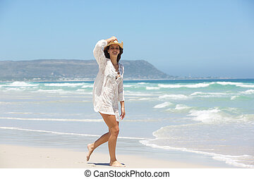 Full length of a young woman walking on beach with hat
