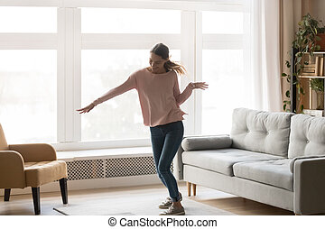 Full-length of active young woman dancing in living room
