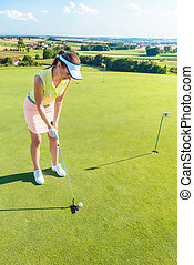 Full length of an attractive woman holding a golf club before hitting the ball