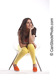 Full length of beautiful young girl sitting in a chair