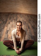 Full length of cheerful lady sitting on the yoga mat and looking happy