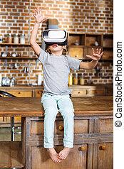 Full length of cheerful little boy wearing VR glasses