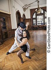 Full Length Of Dancers Performing Tango In Restaurant