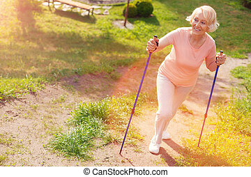 Full length of elderly woman walking through forest