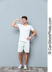 Full length of happy athletic man standing and showing biceps