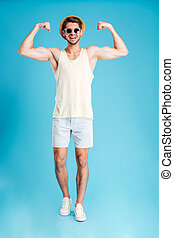 Full length of happy young man standing and showing biceps