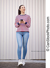 Full length of happy young woman walking and talking with mobile phone