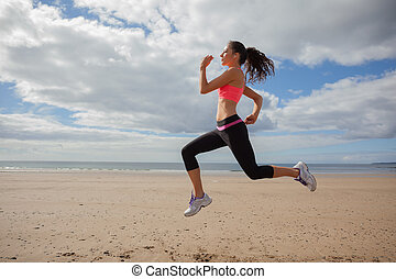 Full length of healthy woman jogging on beach
