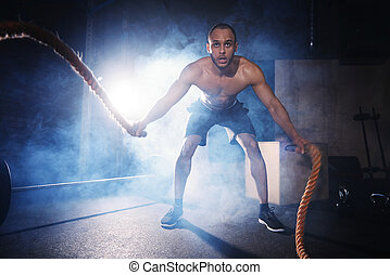 Full length of man exercising with ropes