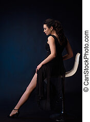 portrait of sensual woman on black dress sitting in a chair