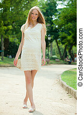 pregnant woman walking in park