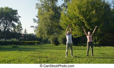 Full length of senior sporty couple doing warm up exercises in the park