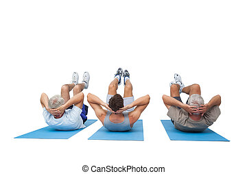 Full length of three men doing abdominal crunches