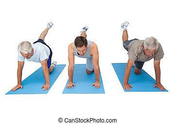 Full length of three men exercising over white background