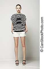 Full Length of Trendy Woman in Shorts and Grey Striped Shirt. Casual Modern Collection