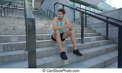 Full-length of very charming athlete with beard wearing black shorts and blue shirt sitting on the stairs resting after jogging, looking at camera