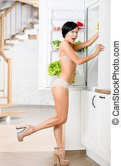 Full length of woman near the opened fridge
