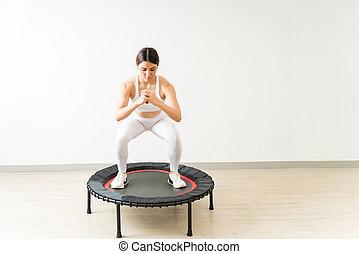 young woman in sportswear jumping on mini trampoline