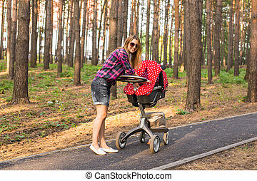 Full length of young mother pushing a stroller in the park
