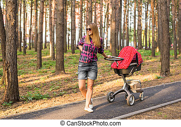 Full length of young mother with a stroller in the park