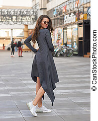 Full length outdoor portrait of woman in gray dress