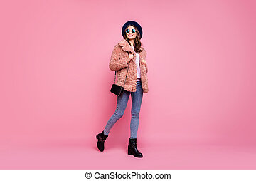 Full length photo of amazing millennial lady going down street watching sightseeing wear stylish jacket jeans shoulder bag sun specs hat isolated pink background