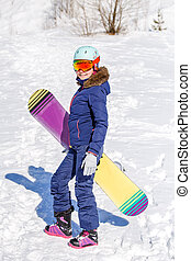 Full-length photo of athletic woman wearing helmet with snowboard