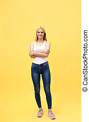 Full length photo of beautiful smiling woman standing with crossed hands, looking at camera, isolated on yellow background.