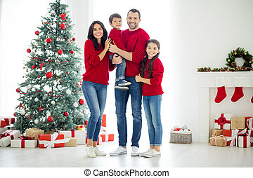 Full length photo of bif gull family charming mommy schoolgirl daddy carrying his little son standing near fireplace enjoy christmas time x-mas holidays in house with newyear decoration indoors