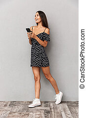 Full length photo of brunette woman in dress smiling and holding mobile phone, isolated over gray background in studio