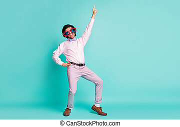 Full length photo of charming brunet curly hair clubber wear pink outfit pointing up empty space isolated teal color background