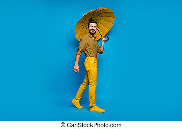 Full length photo of cheerful guy enjoy spring leisure time hold shine colorful parasol wear good look clothes footwear isolated over blue color background