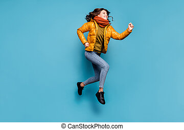 Full length photo of crazy millennial lady jumping high running speed shopping season discounts wear stylish windbreaker jeans scarf pullover isolated blue color background