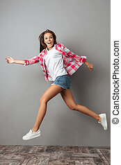Full-length photo of emotional jumping girl in casual wear