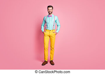 Full length photo of handsome guy trend clothes self-confident worker beaming smile wear teal shirt suspenders bow tie yellow trousers boots socks isolated pastel pink color background