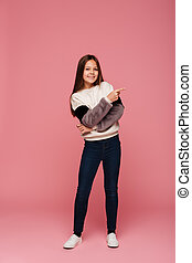 Full-length photo of happy girl pointing aside at copy space isolated