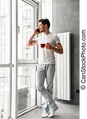 Full length photo of joyful brunette man in casual wear speaking on mobile phone, and looking out the window while holding glass with tea