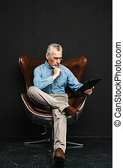 Full length photo of mature smart man working in office while sitting on modern armchair, isolated over black background