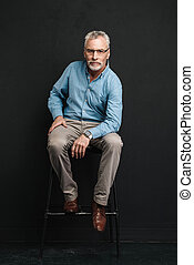 Full length photo of mature stylish man 60s with grey hair and beard sitting on chair in studio and looking on camera, isolated over black background