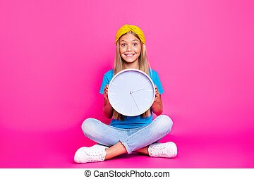 Full length photo of positive cheerful funny funky kid hold clock feel excited wait for start daily routine wear bright denim jeans sneakers, isolated over shine color background