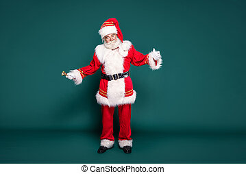 Full length photo of Santa Claus with a golden bell, ringing.