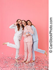 Full length photo of three beautiful teenage women 20s wearing leisure clothings hugging and having fun at slumber party, isolated over pink background