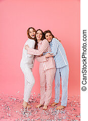 Full length photo of three happy women 20s wearing leisure clothings hugging and having fun at slumber party, isolated over pink background