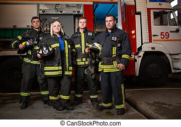 Full-length photo of three young fire men and woman on background of fire truck