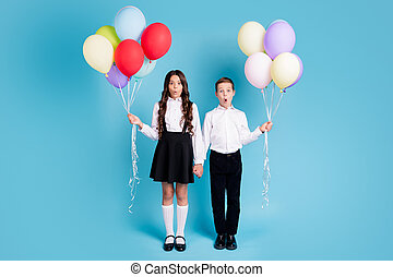 Full length photo of two small girl boy schoolchildren best friends hold hands balloons amazed watch classmates wear white shirt black pants dress shoes isolated blue color background