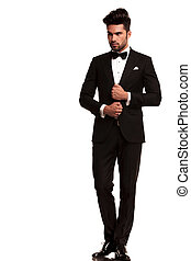 elegant young fashion man adjusting his tuxedo - full length...