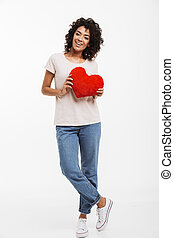 Full length picture of romantic adorable woman 20s with brown hair holding red paper heart in valentine day, isolated over white background