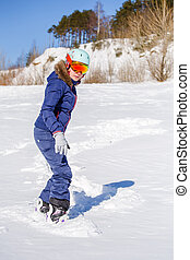 Full-length picture of sporty woman wearing helmet with snowboard on snowy hill