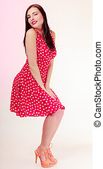 Full length pinup girl brunette woman in retro red dress winking.